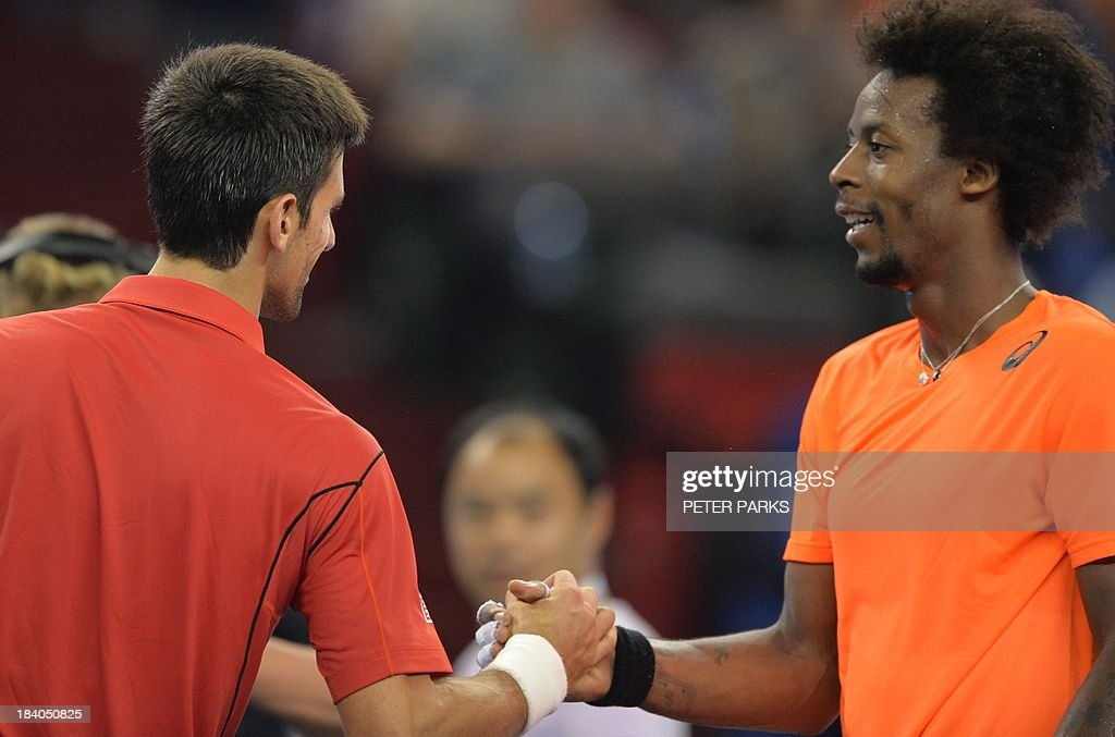 Novak Djokovic of Serbia (L) shakes hands with Gael Monfils of France after their quarter-final match in the Shanghai Masters tennis tournament in Shanghai on October 11, 2013. Djokovic won 6-7, 6-2, 6-4. AFP PHOTO/Peter PARKS