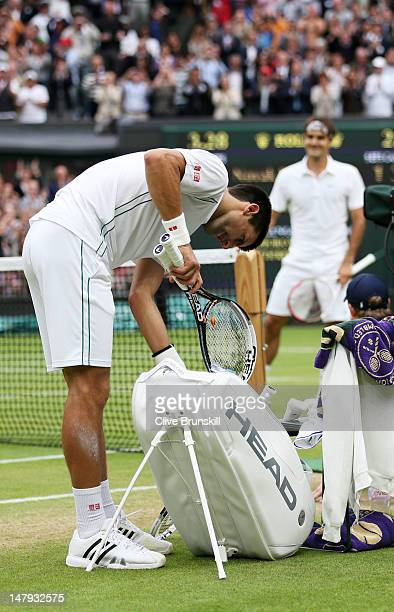Novak Djokovic of Serbia shows his dejection as he packs his bag after losing his Gentlemen's Singles semi final match against Roger Federer of...