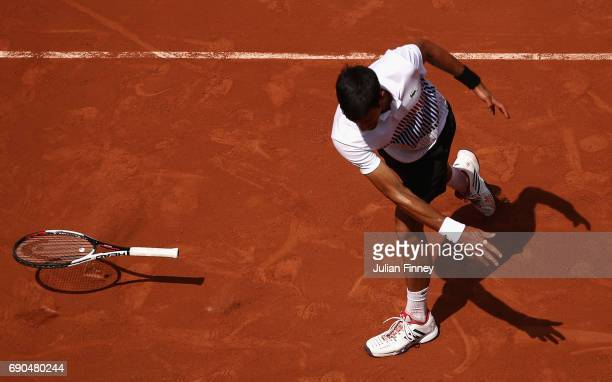 Novak Djokovic of Serbia shows his frustration by throwing his racket onto the court after losing a point during the mens singles second round match...