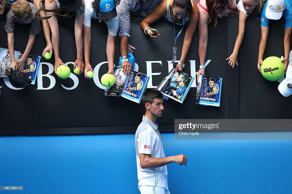 Novak Djokovic of Serbia signs autographs for fans after winning his second round match against Leonardo Mayer of Argentina during day three of the 2014 Australian Open at Melbourne Park on January 15, 2014 in Melbourne, Australia.