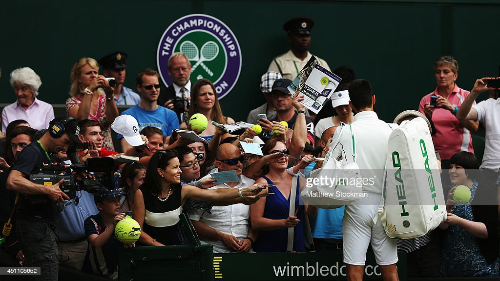 Novak Djokovic of Serbia signs autographs for the fans after defeating Andrey Golubev of Kazakhstan in three straight sets during their Gentlemen's Singles first round match on day one of the Wimbledon Lawn Tennis Championships at the All England Lawn Tennis and Croquet Club at Wimbledon on June 23, 2014 in London, England.