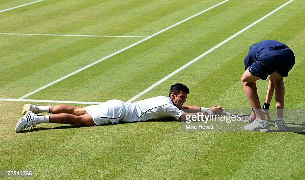 Novak Djokovic of Serbia smiles after falling on the grass as a ballboy picks up his racquet for him during the Gentlemen's Singles semifinal match...