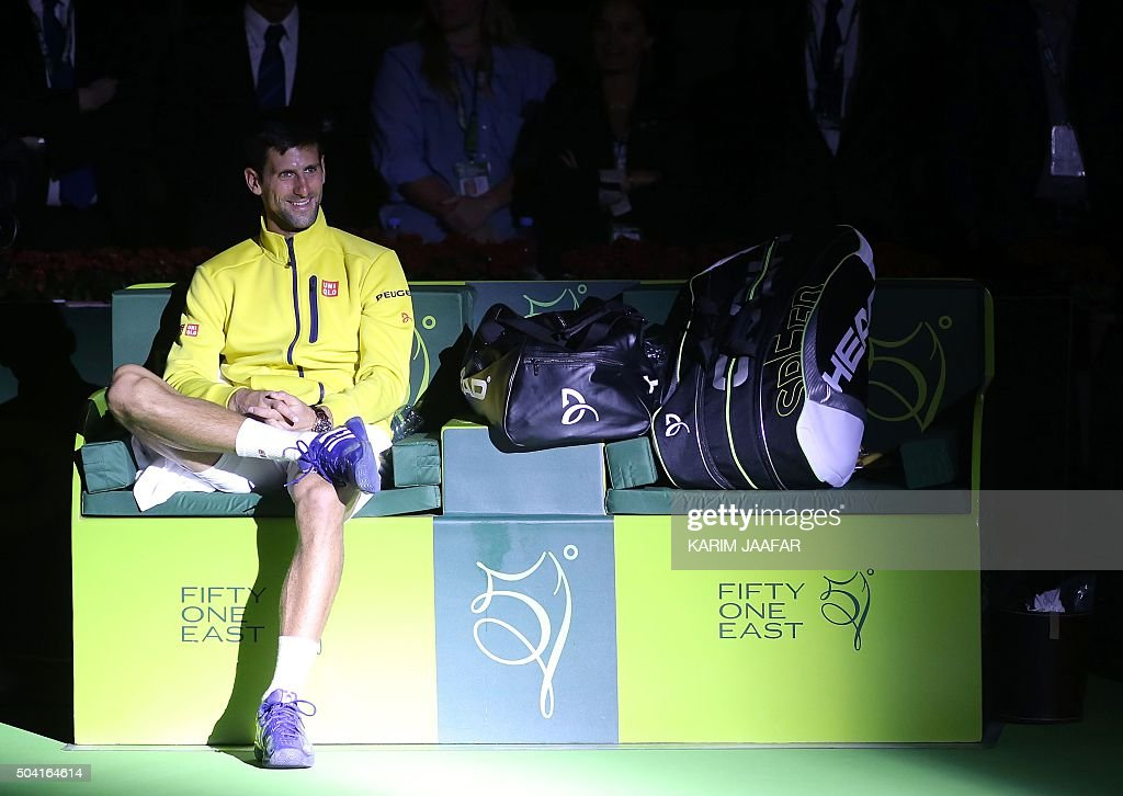 TOPSHOT Novak Djokovic of Serbia smiles as he waits to receive his trophy after beating Rafael Nadal of Spain in the final of the Qatar Open tennis...