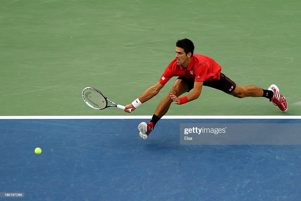 Novak Djokovic of Serbia stertches to play a forehand during his men's singles final match against Rafael Nadal of Spain on Day Fifteen of the 2013...