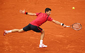 Novak Djokovic of Serbia stretches for a backhand during the Men's Singles first round match against YenHsun Lu of Taipei on day three of the 2016...
