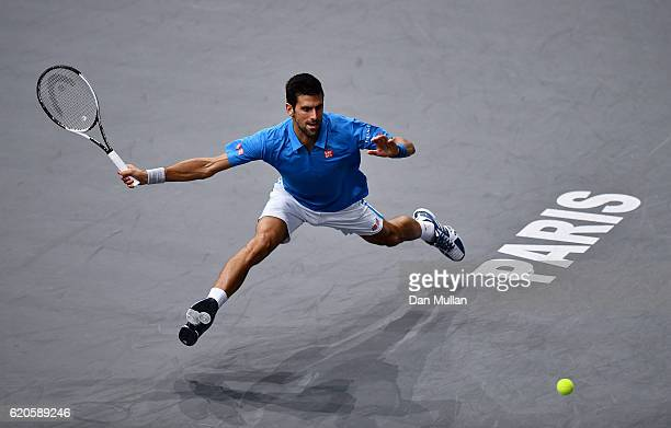 Novak Djokovic of Serbia stretches for a forehand against Gilles Muller of Luxembourg during the Mens Singles second round match on day three of the...