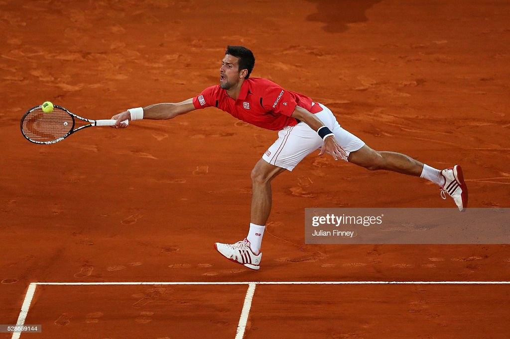 Novak Djokovic of Serbia stretches for a forehand in his match against Milos Raonic of Canada during day seven of the Mutua Madrid Open tennis tournament at the Caja Magica on May 06, 2016 in Madrid, Spain.