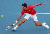 Novak Djokovic of Serbia stretches for the ball during his match against Juan Monaco of Argentina during day two of the AAMI Classic at Kooyong on...