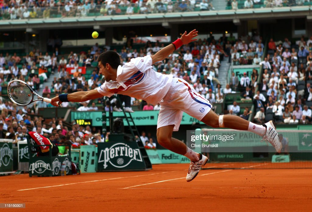 Novak Djokovic of Serbia stretches to hit a backhand during the men's singles semi final match between Roger Federer of Switzerland and Novak Djokovic of Serbia on day thirteen of the French Open at Roland Garros on June 3, 2011 in Paris, France.