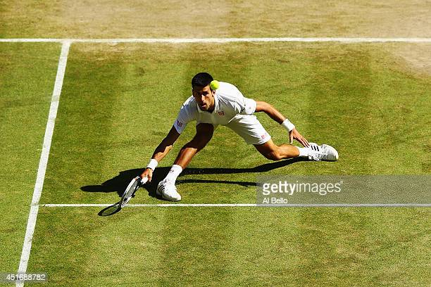Novak Djokovic of Serbia stretches to make a return during his Gentlemen's Singles semifinal match against Grigor Dimitrov of Bulgaria on day eleven...