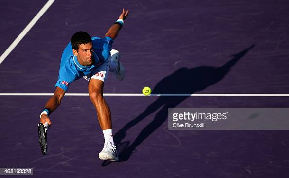 Novak Djokovic of Serbia stretches to play a forehand volley against Steve Darcis of Belgium in their third round match during the Miami Open...