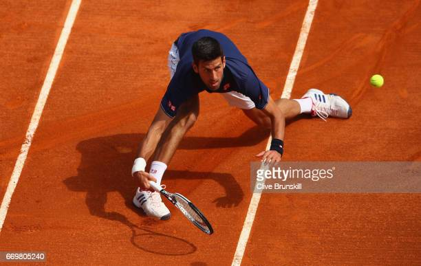 Novak Djokovic of Serbia stretches to play a forehand volley against Gilles Simon of France in his second round match on day three of the Monte Carlo...