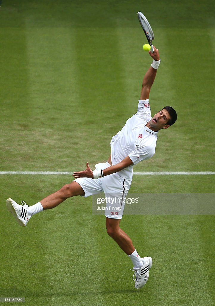 Novak Djokovic of Serbia stretches to smash the ball during his Gentlemen's Singles first round match against Florian Mayer of Germany on day two of the Wimbledon Lawn Tennis Championships at the All England Lawn Tennis and Croquet Club on June 25, 2013 in London, England.