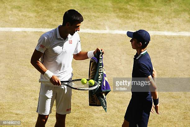 Novak Djokovic of Serbia takes a towel from a ballboy during his Gentlemen's Singles semifinal match against Grigor Dimitrov of Bulgaria on day...