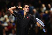 Novak Djokovic of Serbia throws a tennis ball in jest during the exhibition match against Andy Murray of Great Britain on day eight of the Barclays...