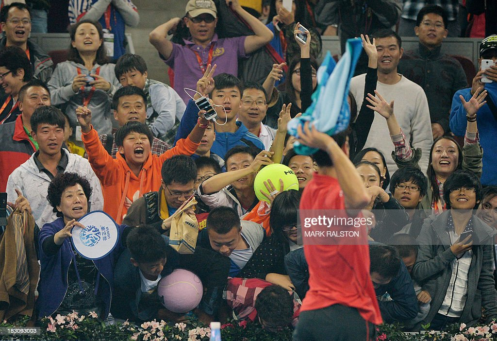 Novak Djokovic of Serbia throws his towel to the crowd after winning his men's singles quarterfinals match against Sam Querrey of USA at the China Open tennis tournament in Beijing on October 4, 2013. Djokovic went on to win 6-1, 6-2. AFP PHOTO / Mark RALSTON