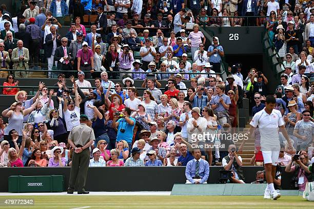 Novak Djokovic of Serbia throws his wrist band to the crowd after winning in his Gentlemens Singles Fourth Round match against Kevin Anderson of...