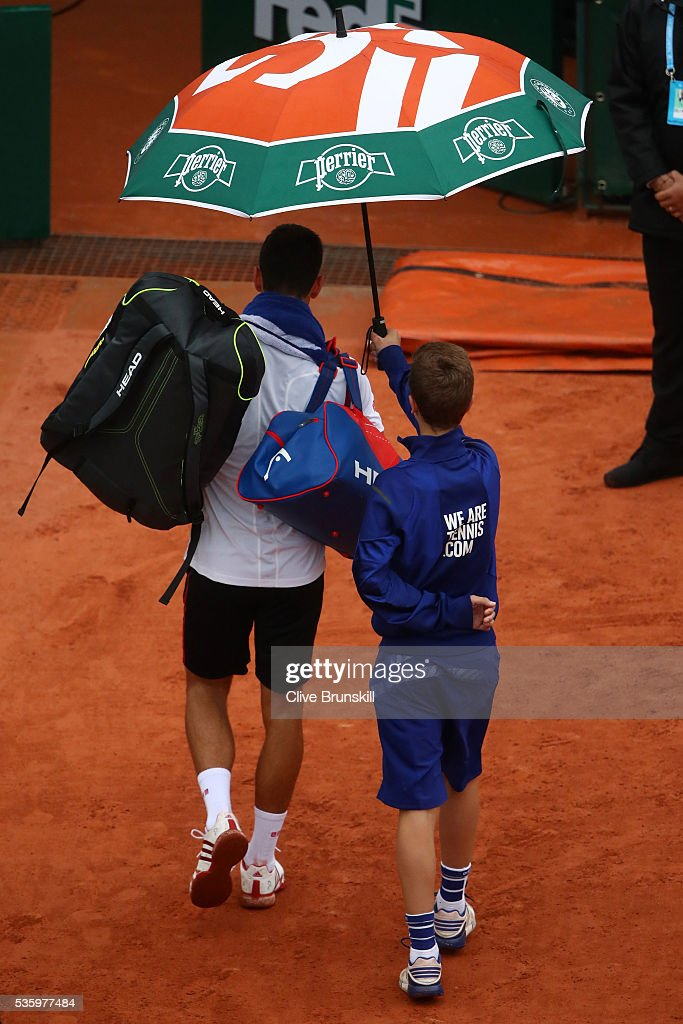 <a gi-track='captionPersonalityLinkClicked' href=/galleries/search?phrase=Novak+Djokovic&family=editorial&specificpeople=588315 ng-click='$event.stopPropagation()'>Novak Djokovic</a> of Serbia walks off court as rain halts play during the Men's Singles fourth round match against Roberto Bautista Agut of Spain on day ten of the 2016 French Open at Roland Garros on May 31, 2016 in Paris, France.