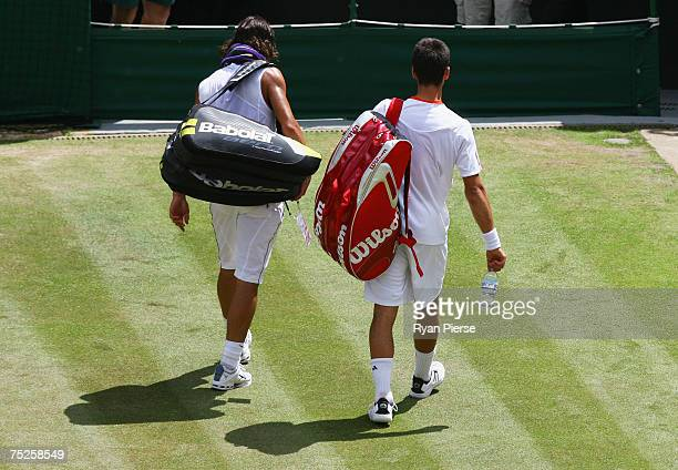Novak Djokovic of Serbia walks off of court with Rafael Nadal of Spain as he retires from the match due to injury during the Men's Singles semifinal...