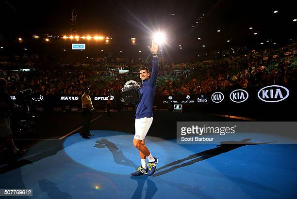 Novak Djokovic of Serbia waves to the crowd as he holds the Norman Brookes Challenge Cup after winning the Men's Singles Final over Andy Murray of...