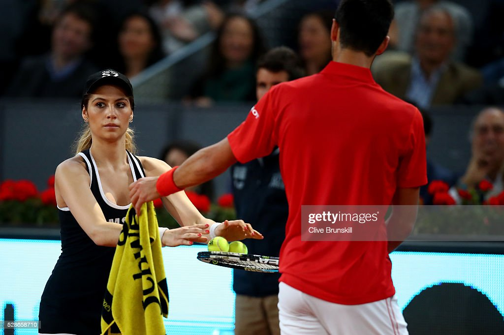 Novak Djokovic of Serbia with a glamorous model ball girl in his quarter final round match against Milos Raonic of Canada during day seven of the Mutua Madrid Open tennis tournament at the Caja Magica on May 06, 2016 in Madrid,Spain.