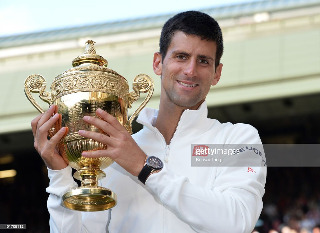 Novak Djokovic poses with the winners trophy after beating Roger Federer on centre court during the mens singles final of the Wimbledon Championships at Wimbledon on July 6, 2014 in London, England.