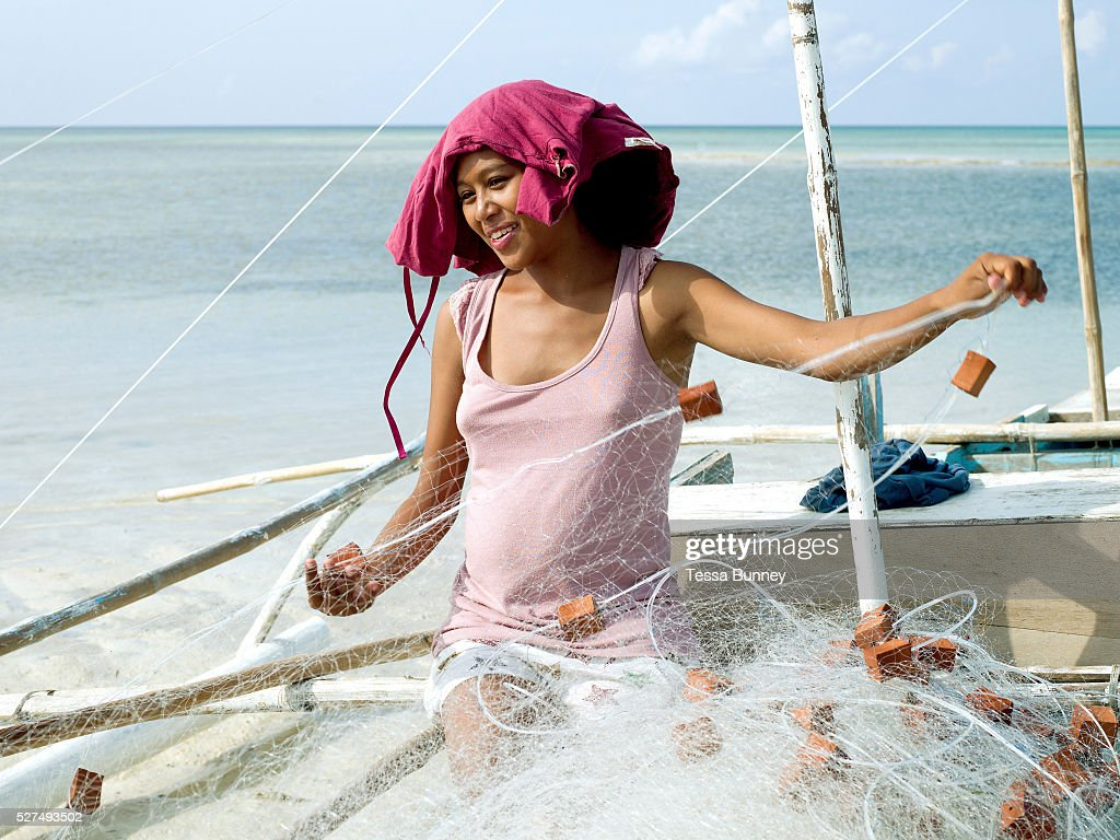 Noveline Pinote the pregnant wife of a fisherman prepares the fishing nets on her husbands pump boat Pooc Bantayan Island The Philippines On November...