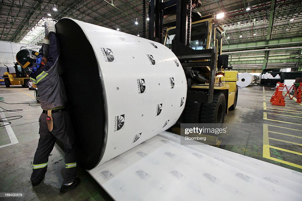 A Novelis Inc. employee encloses a roll of aluminum foil with packaging at the company's production facility in Yeongju, South Korea, on Thursday, May 23, 2013. Novelis plans to boost research and development staff by 40 percent as the biggest supplier of flat-rolled aluminum products to global carmakers seeks to increase recycled content in products used in cans and vehicles. Photographer: Woohae Cho/Bloomberg via Getty Images