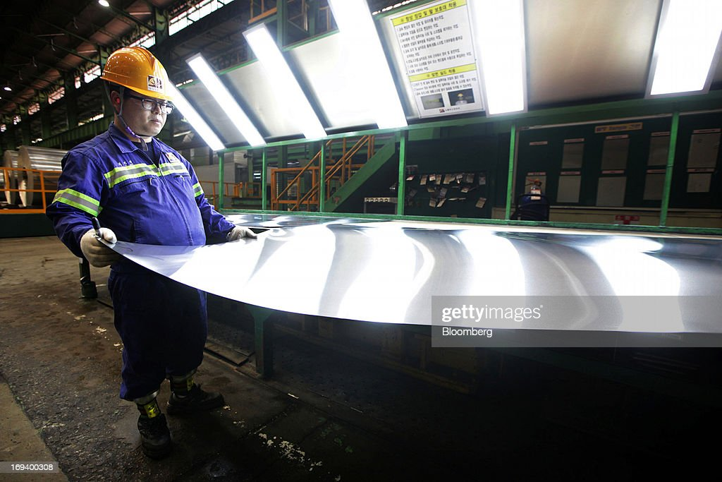 A Novelis Inc. employee inspects a roll of aluminum after cold rolling at the company's production facility in Yeongju, South Korea, on Thursday, May 23, 2013. Novelis plans to boost research and development staff by 40 percent as the biggest supplier of flat-rolled aluminum products to global carmakers seeks to increase recycled content in products used in cans and vehicles. Photographer: Woohae Cho/Bloomberg via Getty Images