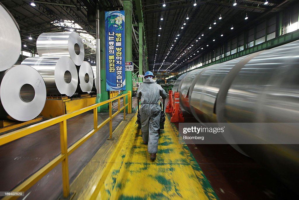 A Novelis Inc. employee walks past rolls of sheet aluminum that sit stored ahead of cold rolling at the company's production facility in Yeongju, South Korea, on Thursday, May 23, 2013. Novelis plans to boost research and development staff by 40 percent as the biggest supplier of flat-rolled aluminum products to global carmakers seeks to increase recycled content in products used in cans and vehicles. Photographer: Woohae Cho/Bloomberg via Getty Images