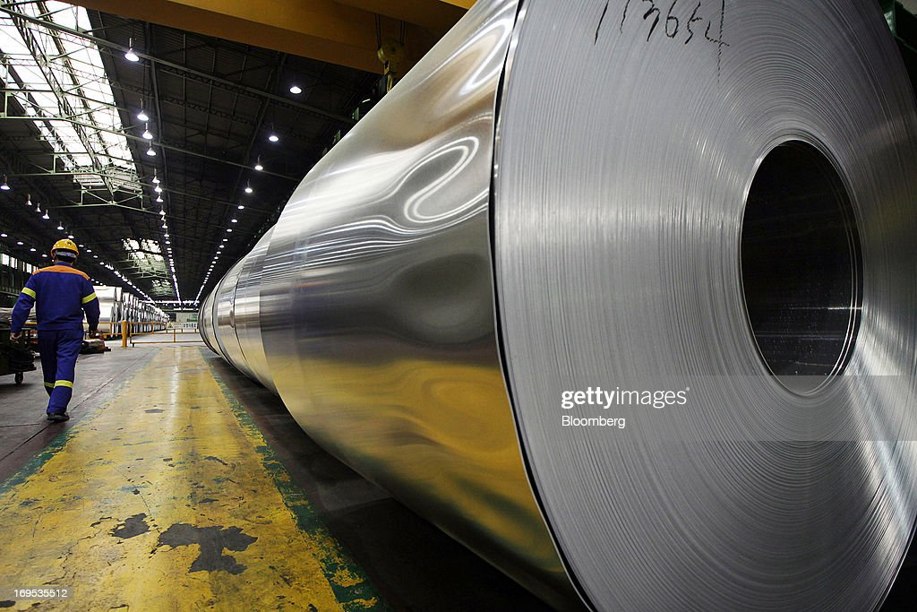 A Novelis Inc. employee walks past rolls of sheet aluminum that sit stored ahead of cold rolling at the company's production facility in Yeongju, South Korea, on Thursday, May 23, 2013. Novelis plans to boost research and development staff by 40 percent as the biggest supplier of flat-rolled aluminum products to global carmakers seeks to increase recycled content in products used in cans and vehicles. Photographer: Woohae CHO for Bloomberg Woohae Cho/Bloomberg via Getty Images