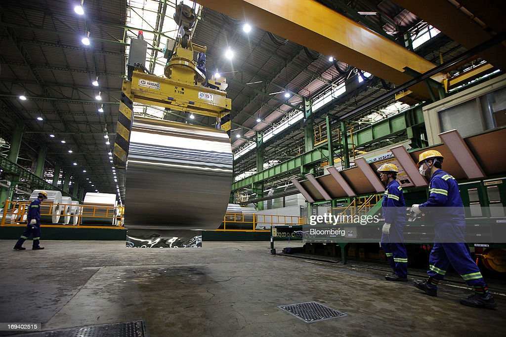 Novelis Inc. employees approach a crane held roll of sheet aluminum after cold rolling at the company's production facility in Yeongju, South Korea, on Thursday, May 23, 2013. Novelis plans to boost research and development staff by 40 percent as the biggest supplier of flat-rolled aluminum products to global carmakers seeks to increase recycled content in products used in cans and vehicles. Photographer: Woohae Cho/Bloomberg via Getty Images