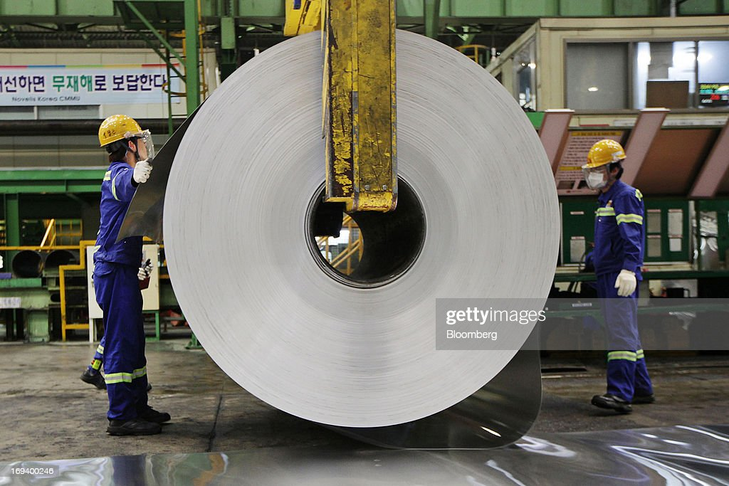 Novelis Inc. employees inspect a roll of sheet aluminum at the company's production facility in Yeongju, South Korea, on Thursday, May 23, 2013. Novelis plans to boost research and development staff by 40 percent as the biggest supplier of flat-rolled aluminum products to global carmakers seeks to increase recycled content in products used in cans and vehicles. Photographer: Woohae Cho/Bloomberg via Getty Images