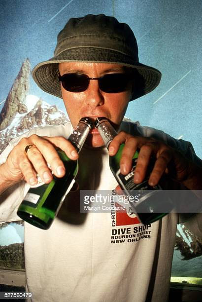Novelist Irvine Welsh portrait holding two bottles of lager United Kingdom 1995