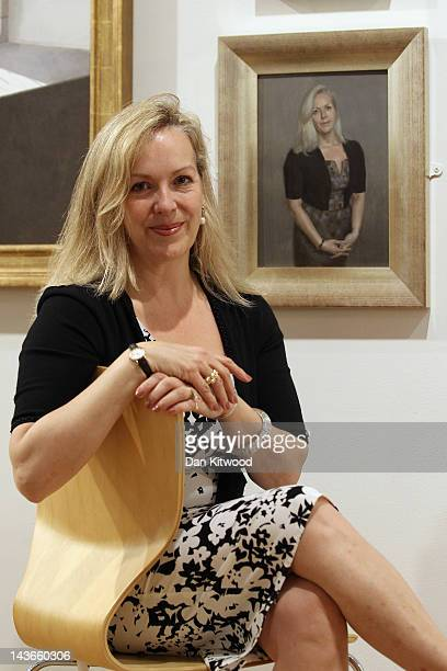 Novelist Isabel Woolf poses besides a painting of herself during a photocall for the Royal Society of Portrait Painters exhibition at the Mall...