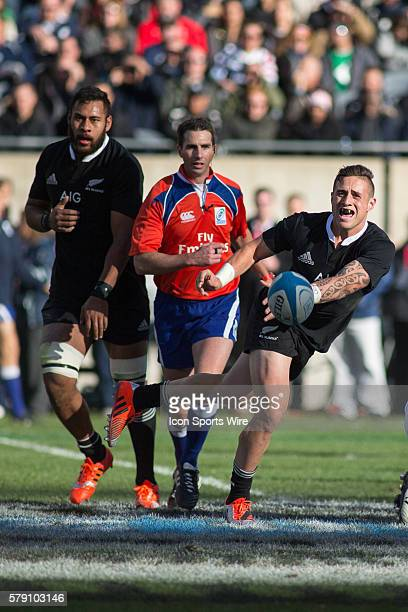 All Black scrumhalf TJ Perenara passes the ball as the referee and All Black lock Patrick Tuipulotu look on during the game between the New Zealand...