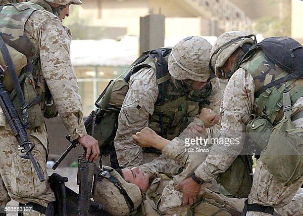 November 10th 2004––Fallouja Iraq––Members of Charlie Company of the First Marine Division Eighth Regiment tend to a comrade wounded by sniper fire...