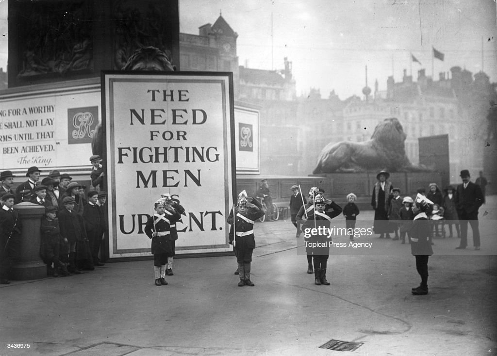 In Trafalgar Square London street urchins dressed as soldiers with paper hats and canes as guns stand to attention watched by a small crowd Behind...