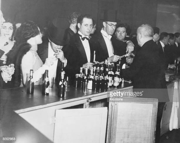 Evening dressed revellers buying their drinks at a bar at the time of prohibition