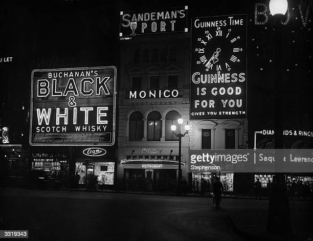 Night time in Piccadilly Circus London with its neon advertising signs including a Guinness clock