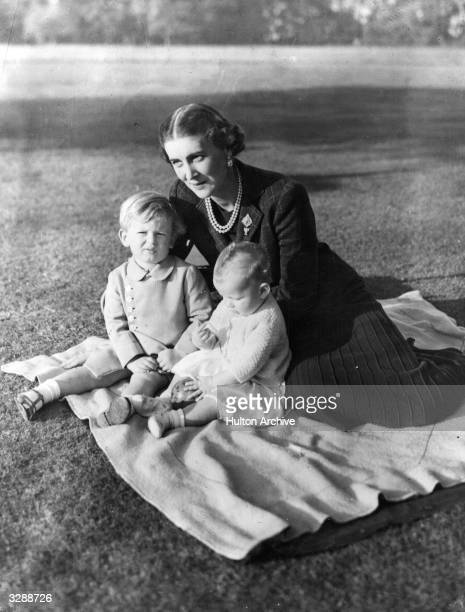 The Duchess Marina of Kent sitting on a rug on the lawn with her two children Prince Edward and Princess Alexandra at 'Coppins' in Iver...