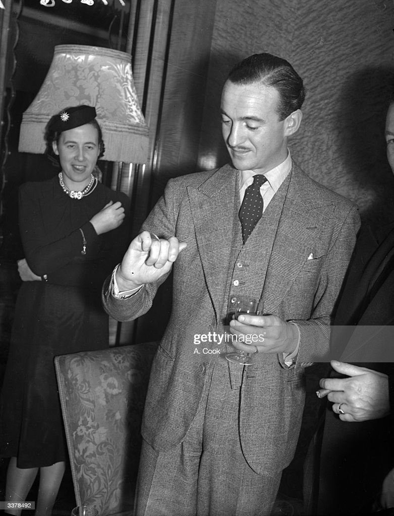 Film star David Niven (1910 - 1983) doing a coin trick at a reception.