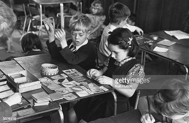 A young boy and girl sit arranging cards in a classroom at a 'Montessori' school in Acton London Original Publication Picture Post 4244 The Woman Who...