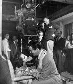 A film crew looking towards American actors Robert and Elizabeth Taylor as they embrace on the set of 'Conspirator' a Metro Goldwyn Mayer production