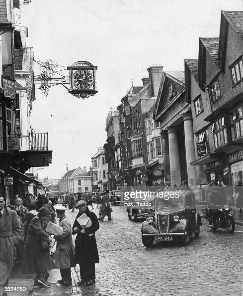 Newspaper vendor C Bicknell making a sale in the High Street Guildford Surrey Beside him is another wellknown news vendor