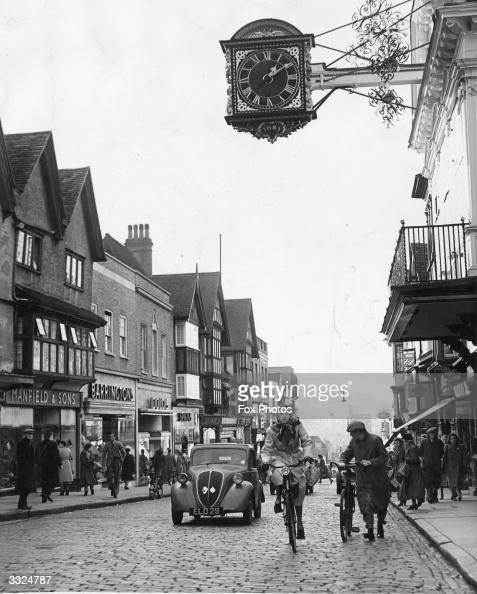 Passersby and cyclists in the High Street Guildford Surrey On the right is the Guildhall Clock which dates from 1683