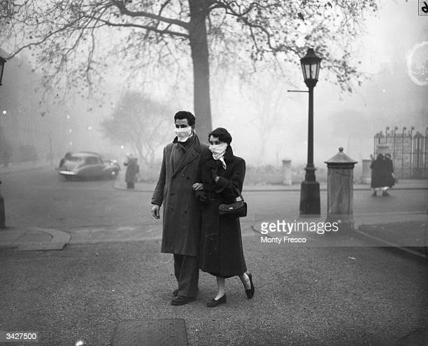 A couple walking in London wearing smog masks on a foggy day