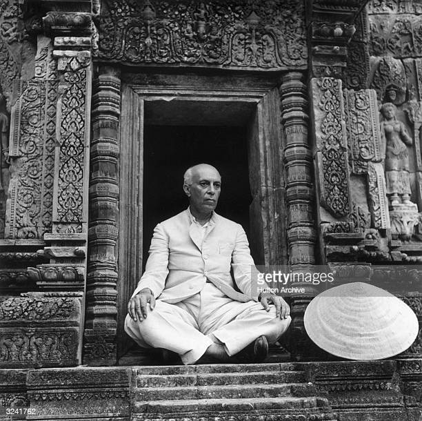 Indian Prime Minister Jawaharlal Nehru sits in the doorway of the Banteay Srei Temple during a visit to Indochina