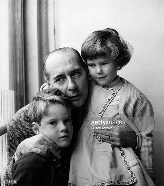 Italian film director Roberto Rossellini stands by a window holding his son Roberto and his daughter Isotta at their home in Rome Italy