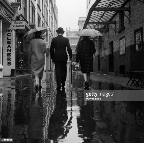 This city gent has forgotten what his umbrella is for as the rain falls on the streets of London